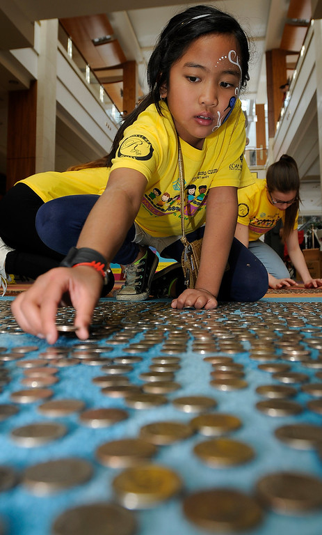 . Viviene Carvajal,8, puts quarters on the floor during the 6th Annual Mile of Quarters event that was held at Westfield Topanga Mall to benefit the Boys and Girls Club of the West Valley. The quarters were laid out on the floor on specially marked carpet, with one square foot equaling $3.25. When the entire mile of quarters is completed, $17,160 will be laid out on the floor. Woodland Hills, CA 2/23/2013(John McCoy/Staff Photographer)