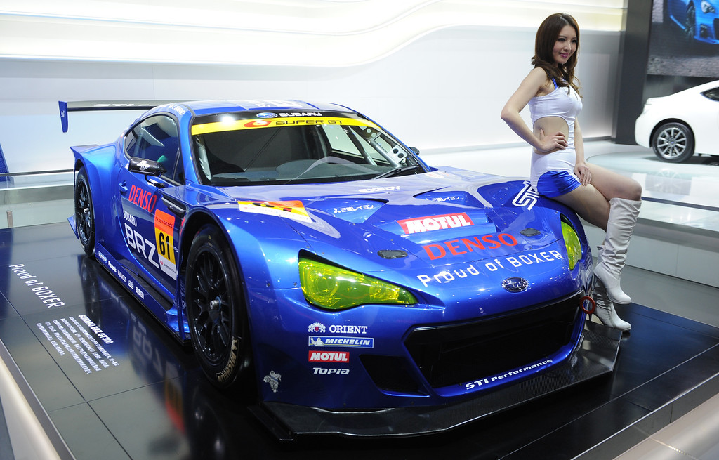 . This photo taken on April 20, 2013 shows a model posing next to a Subaru BRZ racing car on media day at the Shanghai auto show. The Shanghai auto show, which opens to the public on April 21, is expected to attract more than 800,000 visitors over the course of nine days.   PETER PARKS/AFP/Getty Images