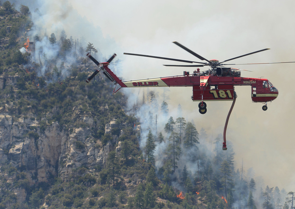 . A firefighting helicopter drops water on a forest fire in Oak Creak Canyon in Sedona, Az., on Thursday May 22, 2014. The human-caused Slide Fire started Tuesday. (AP Photo/Vyto Starinskas)