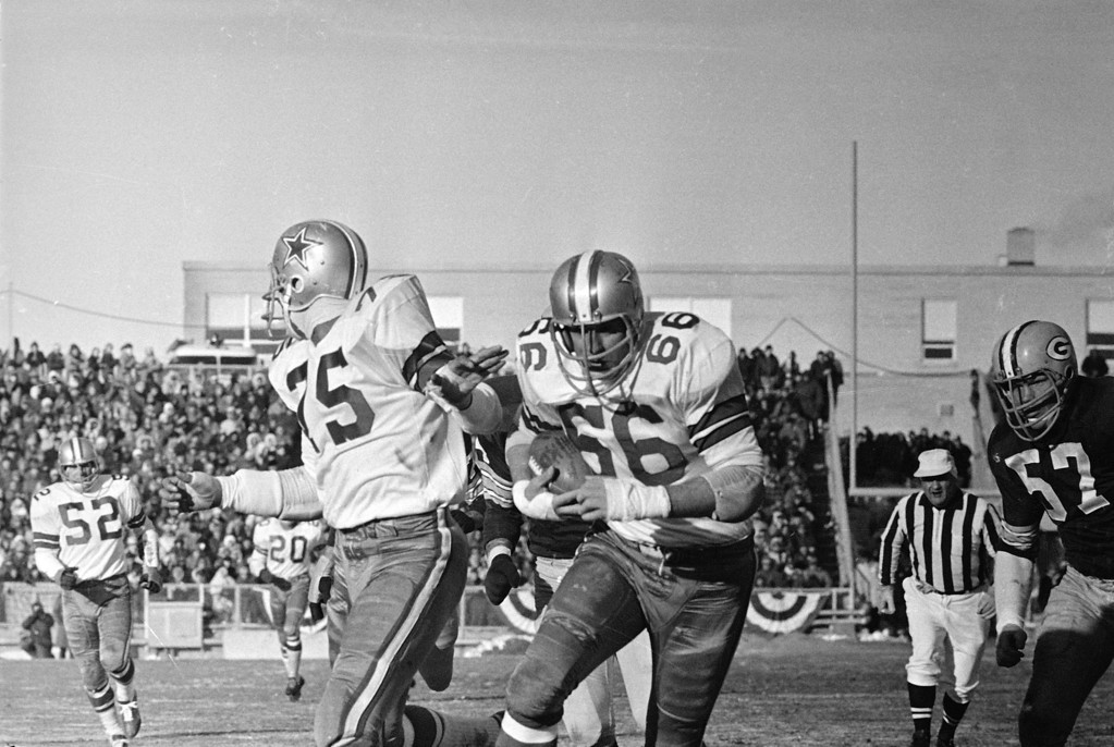 . After picking up the ball fumbled by Green Bay Packers quarterback Bart Starr, Dallas Cowboys defensive end George Andrie (66) follows teammate Jethro Pugh (75) over the goal line to score in second quarter of the NFL championship game on December 31, 1967 at Green Bay. (AP Photo)