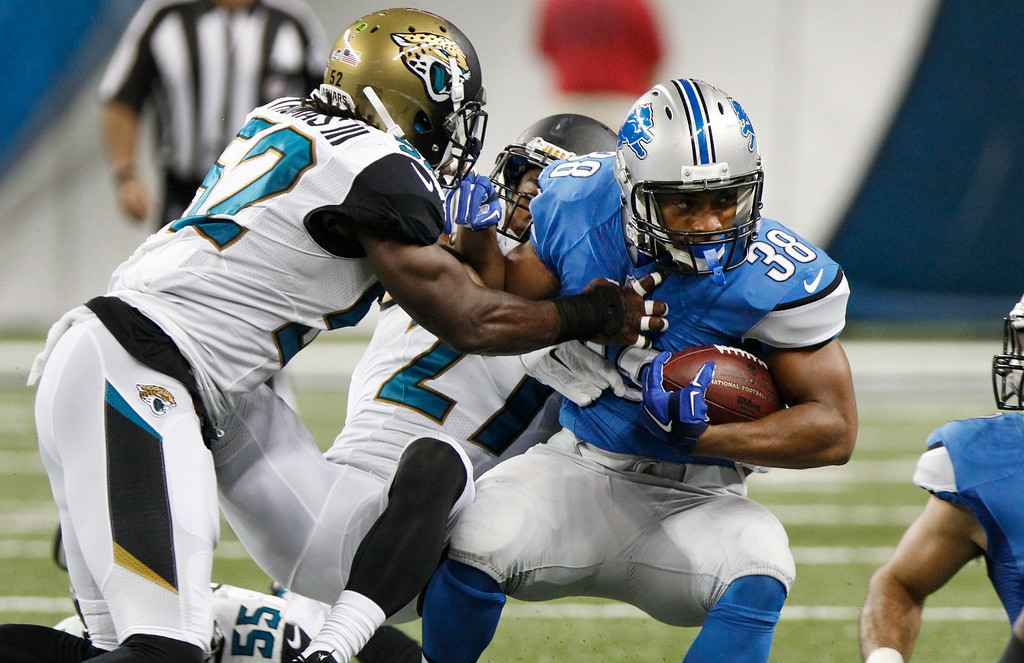 . Detroit Lions running back George Winn (38) fights for yardage as Jacksonville Jaguars outside linebacker J.T. Thomas (52) makes the tackle in the first half of a preseason NFL football game at Ford Field in Detroit, Friday, Aug. 22, 2014.  (AP Photo/Duane Burleson)