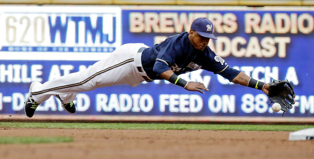 . Milwaukee Brewers shortstop Jean Segura makes a diving try at a single hit by Colorado Rockies\' Michael McKenry during the third inning of a baseball game Friday, June 27, 2014, in Milwaukee. (AP Photo/Morry Gash)