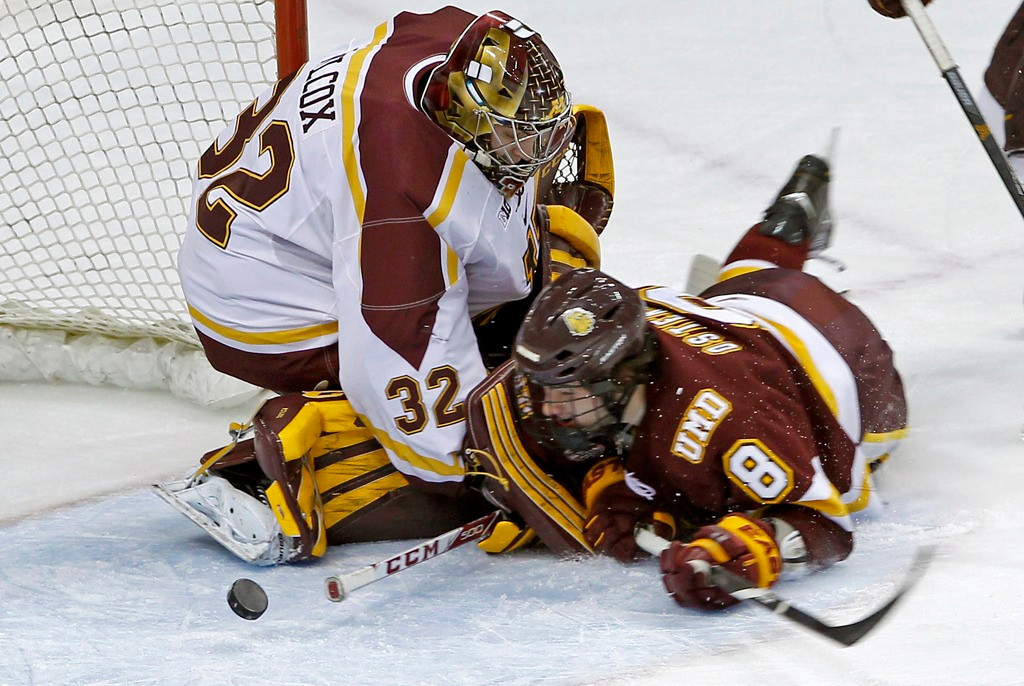 . Bulldogs left wing Kyle Osterberg, right, collides with Gophers goalie Adam Wilcox, who deflects Osterberg\'s shot during the first period. (AP Photo/Ann Heisenfelt)