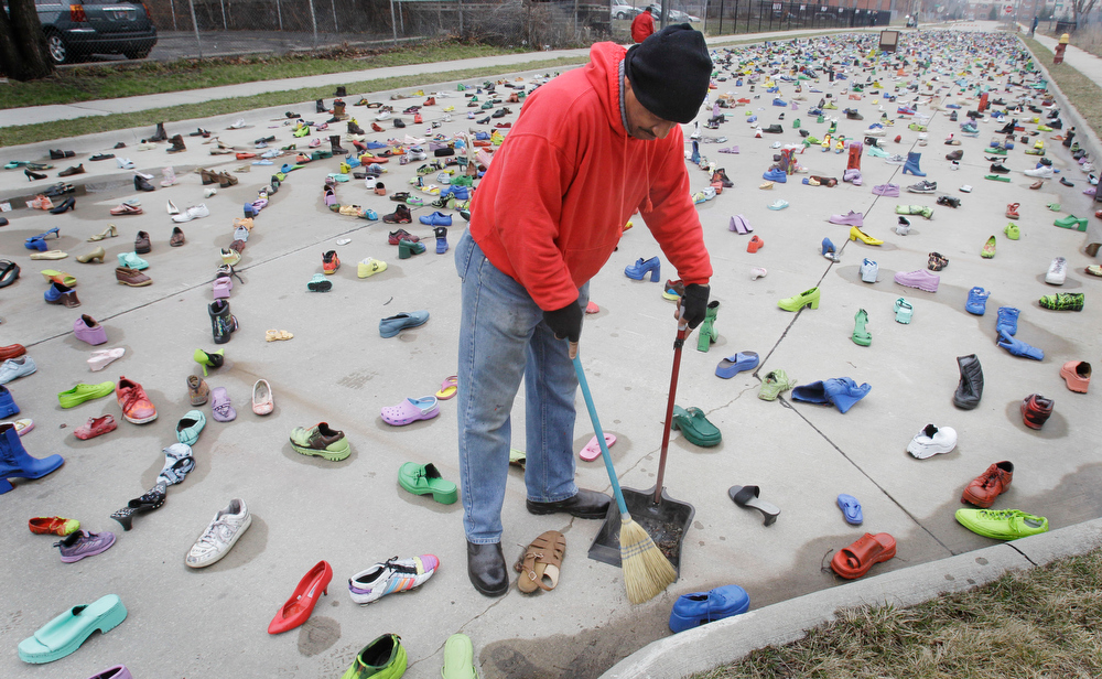 "Description of . Artist Tyree Guyton cleans up his art project called ""Street Folk\"" on Edmund Place in Detroit, Thursday, April 7, 2011. Guyton says \""the shoes are a reflection of people, all going in different directions and yet they are all in the streets.\"" (AP Photo/Carlos Osorio)"