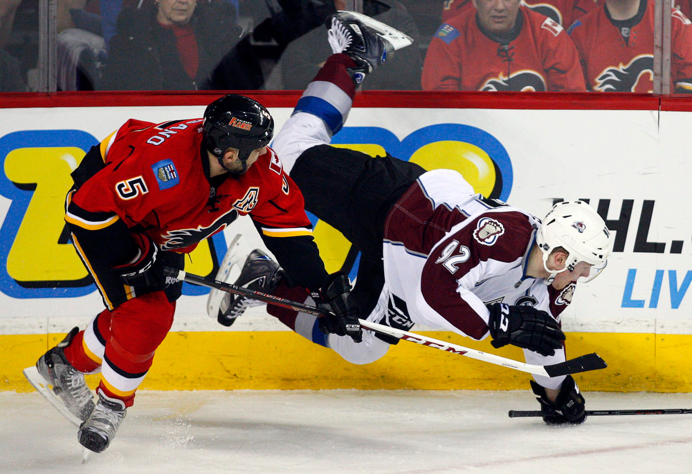 . Colorado Avalanche\'s Gabriel Landeskog, right, of Sweden, crashes to the ice after a check from Calgary Flames\' Mark Giordano during the first period of their NHL hockey game in Calgary, Alberta, Wednesday, March 27, 2013. (AP Photo/The Canadian Press, Jeff McIntosh)