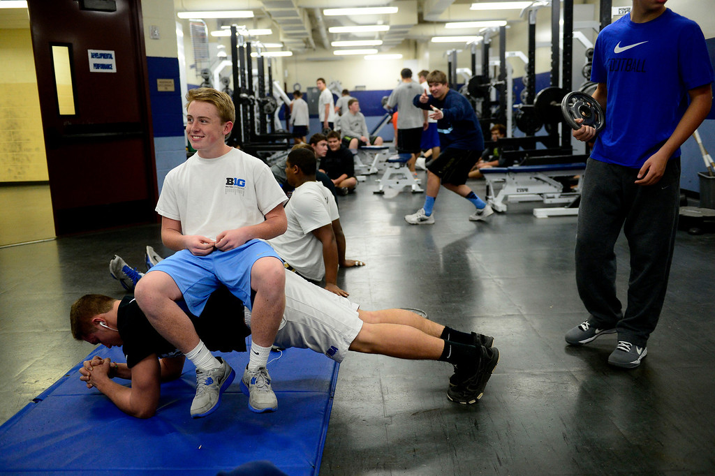 . Linebacker Eliot Benedict sits on fellow linebacker Justin Falls as he does planks during practice. (Photo by AAron Ontiveroz/The Denver Post)