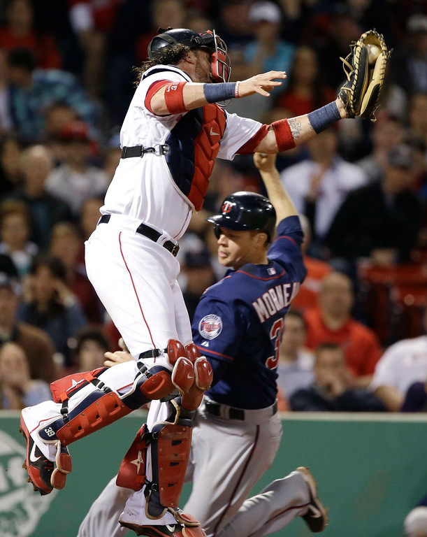 . Boston Red Sox catcher Jarrod Saltalamacchia catches a high throw but cannot make a tag as Minnesota Twins\' Justin Morneau slides in to score on a grounder by Ryan Doumit during the eighth inning of a baseball game at Fenway Park in Boston, Tuesday, May 7, 2013. (AP Photo/Elise Amendola)