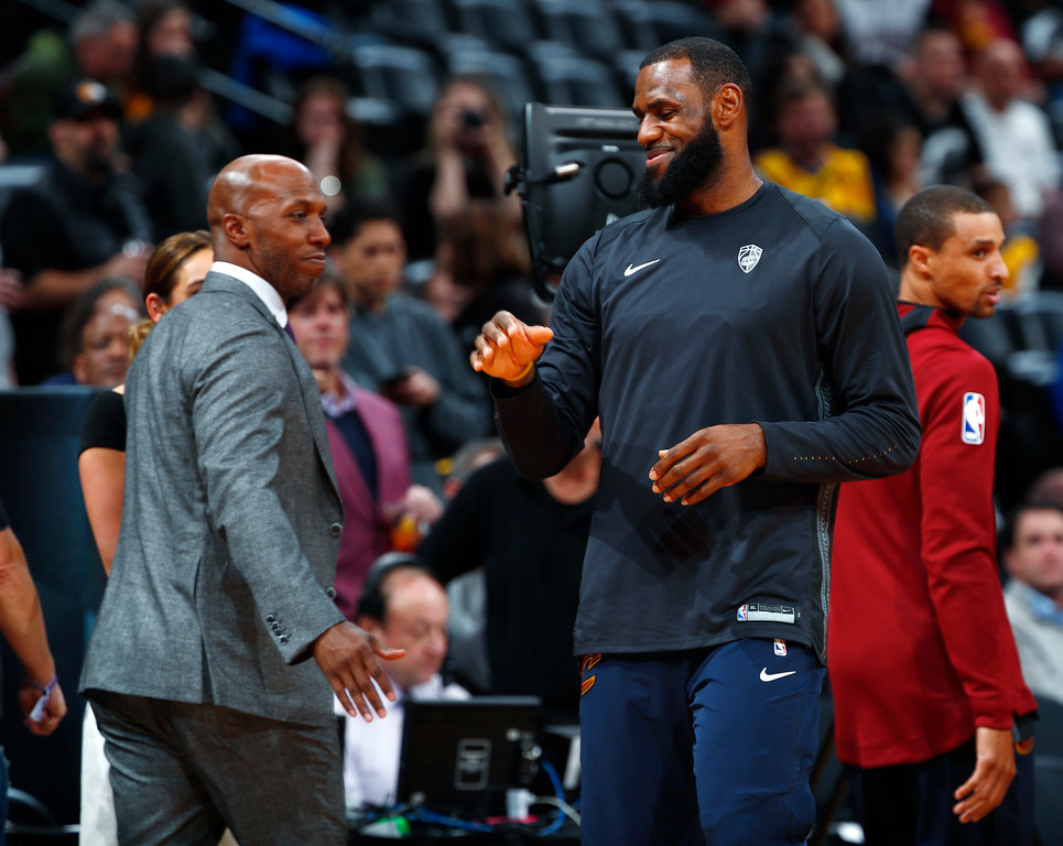. Cleveland Cavaliers forward LeBron James, right, greets television announcer and retired NBA player Chauncey Billups as the Cavaliers warm up to face the Denver Nuggets in an NBA basketball game Wednesday, March 7, 2018, in Denver. (AP Photo/David Zalubowski)
