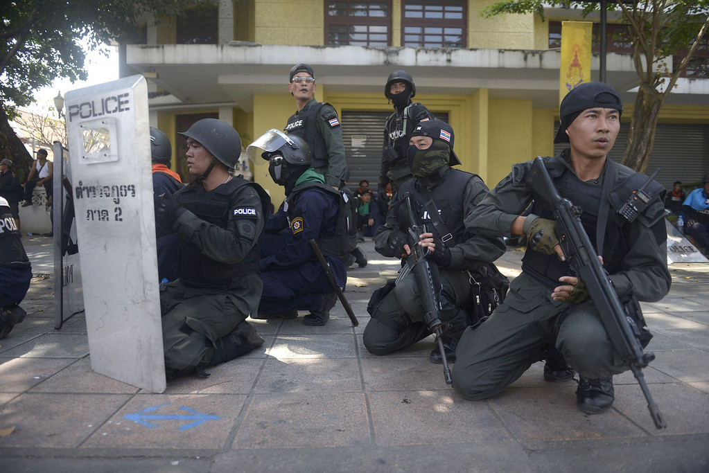 . Thai Police take cover on a street near Phan fah Bridge after grenade explosions and gunfire killed one officer and seriously injuring several police offers during the police operation to reclaim the protest site on February 18, 2014 in Bangkok, Thailand.  (Photo by Nick McGrath/Getty Images)