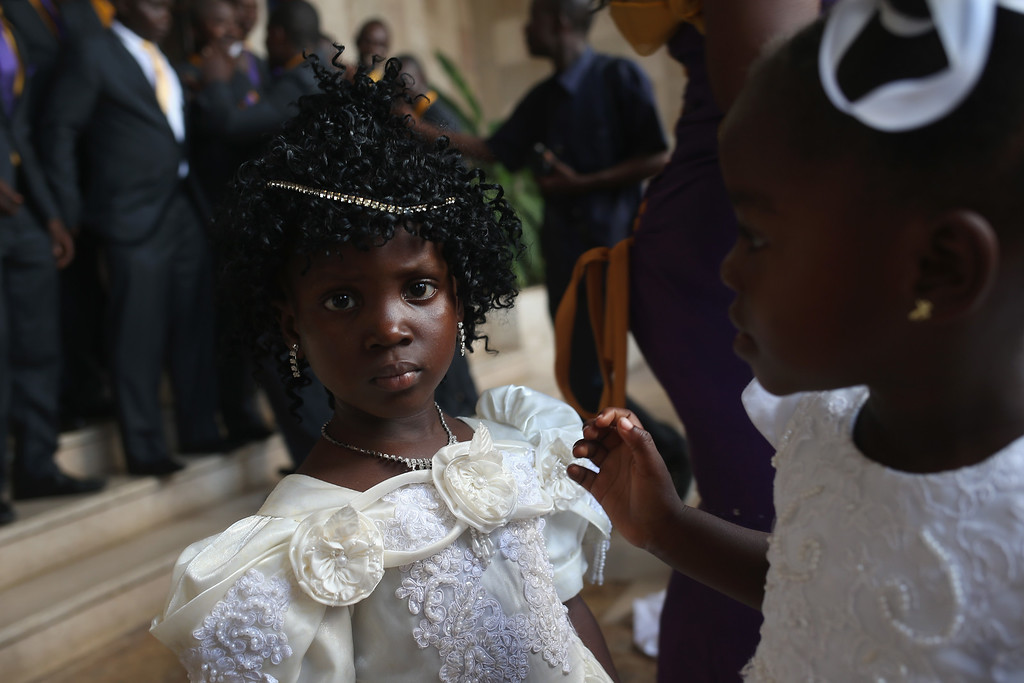 . Flower girls prepare to enter a wedding reception on January 24, 2015 in Monrovia, Liberia. The bride and groom had waited until the worst of the Ebola epidemic had passed before scheduling their wedding. In order to control the worst Ebola outbreak in history, the government and international aid agencies discouraged public gatherings and physical touching. With Ebola cases now in single digits nationwide, people have begun to return to normal life.  (Photo by John Moore/Getty Images)