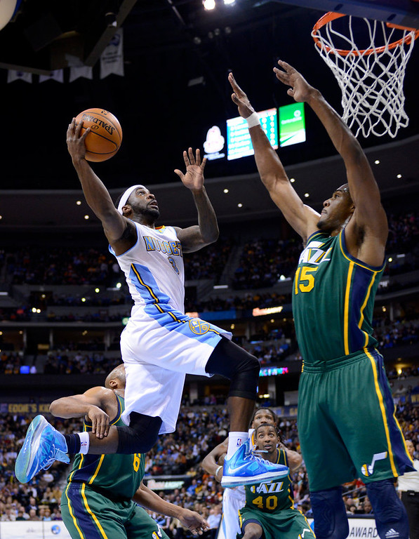 . Denver Nuggets guard Ty Lawson (3) goes up for a shot against Utah Jazz forward Derrick Favors (15) during the second quarter of an NBA basketball game on Saturday, Jan. 5, 2013, in Denver. (AP Photo/Jack Dempsey)