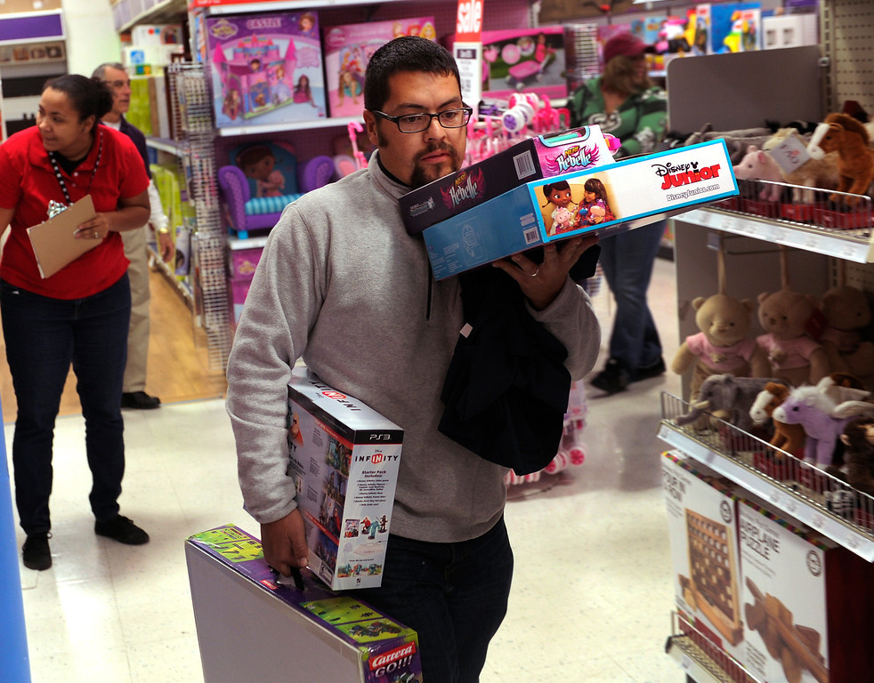 . Reuben Herrera balanced items as he headed for a cashier at the Toys R Us store on County Line Road in Arapahoe County Thursday night, November 28, 2013. Many metro area stores got a jump on Black Friday by opening on Thursday. Photo By Karl Gehring/The Denver Post