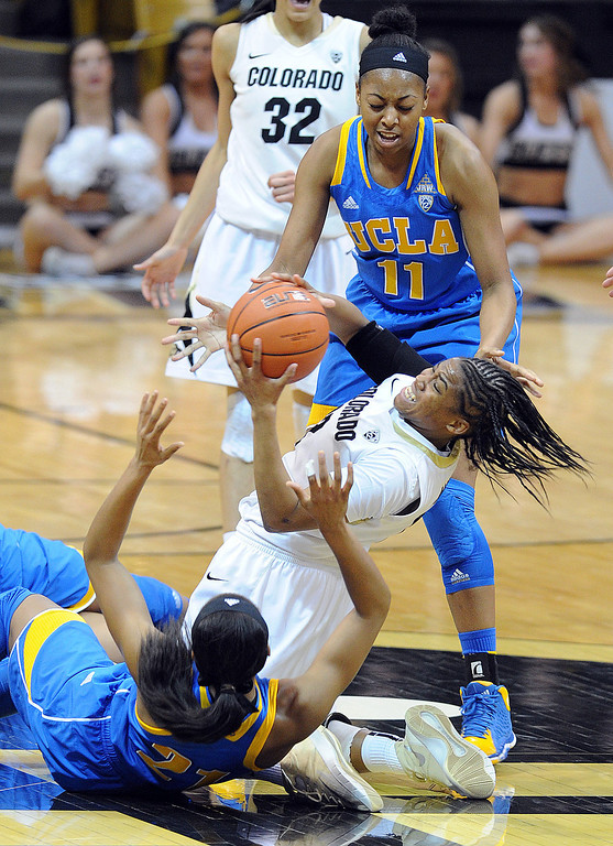 . Colorado\'s Ashley Wilson, center, comes up with the ball after a struggle with UCLA\'s Nirra Fields, bottom, and Atonye Nyingifa during the second half of an NCAA college basketball game Friday, Feb. 28, 2014, in Boulder, Colo. Colorado won 62-42. (AP Photo/Daily Camera, Cliff Grassmick)