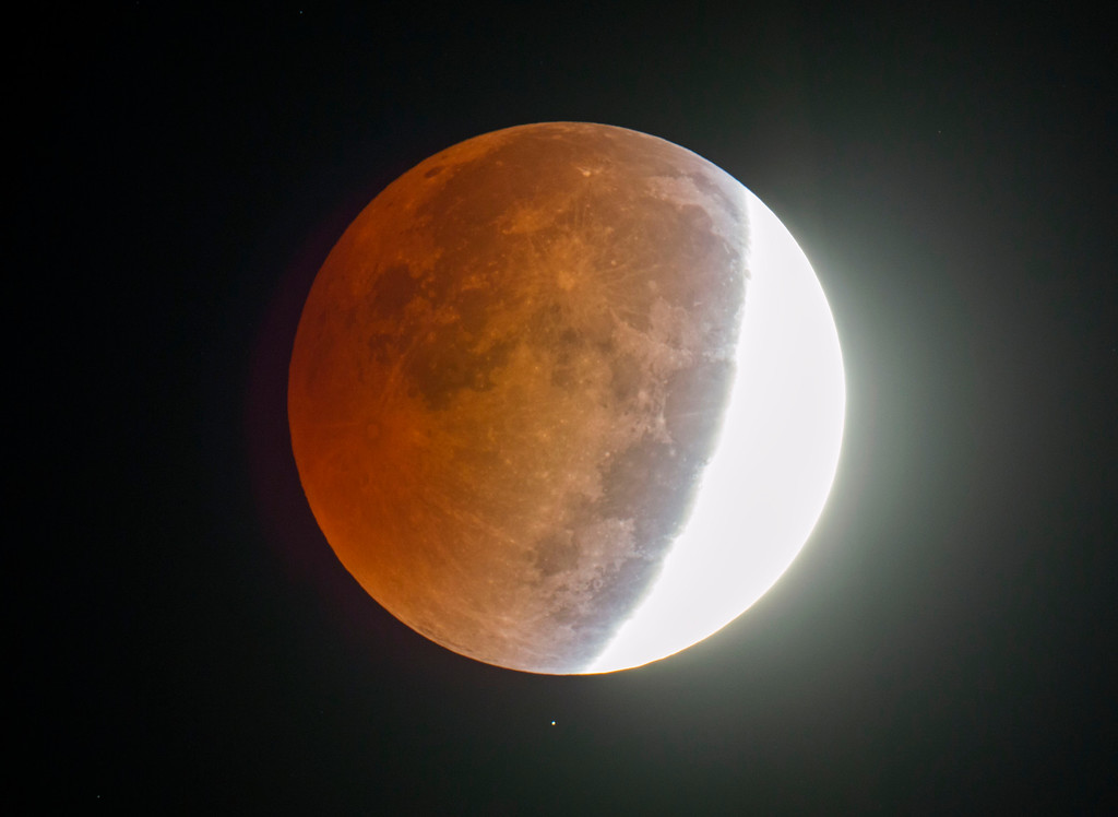 . A lunar eclipse appears above Wade, N.C.  in a picture made through an amateur astronomer\'s 8-inch telescope on Wednesday, Oct. 8, 2014.  The moon appears orange or red, the result of sunlight scattering off Earth\'s atmosphere. This is known as the blood moon. (AP Photo/The Fayetteville Observer, Johnny Horne)