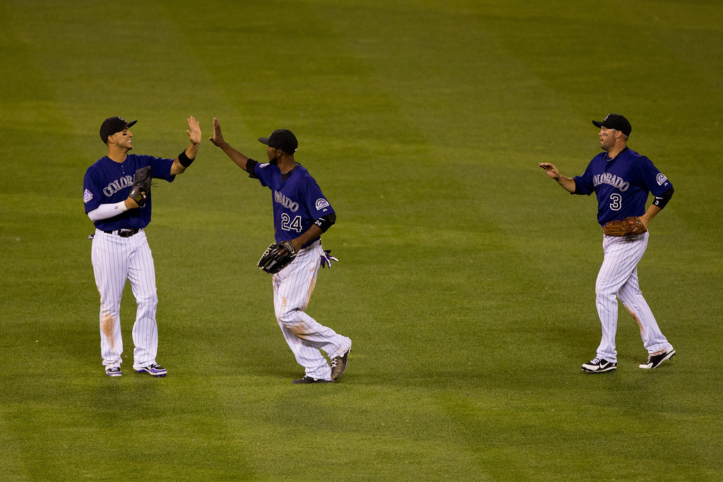 . DENVER, CO - JULY 20:  Carlos Gonzalez #5, Dexter Fowler #24 and Michael Cuddyer #3 of the Colorado Rockies celebrate after defeating the Chicago Cubs 9-3 at Coors Field on July 20, 2013 in Denver, Colorado.  (Photo by Justin Edmonds/Getty Images)