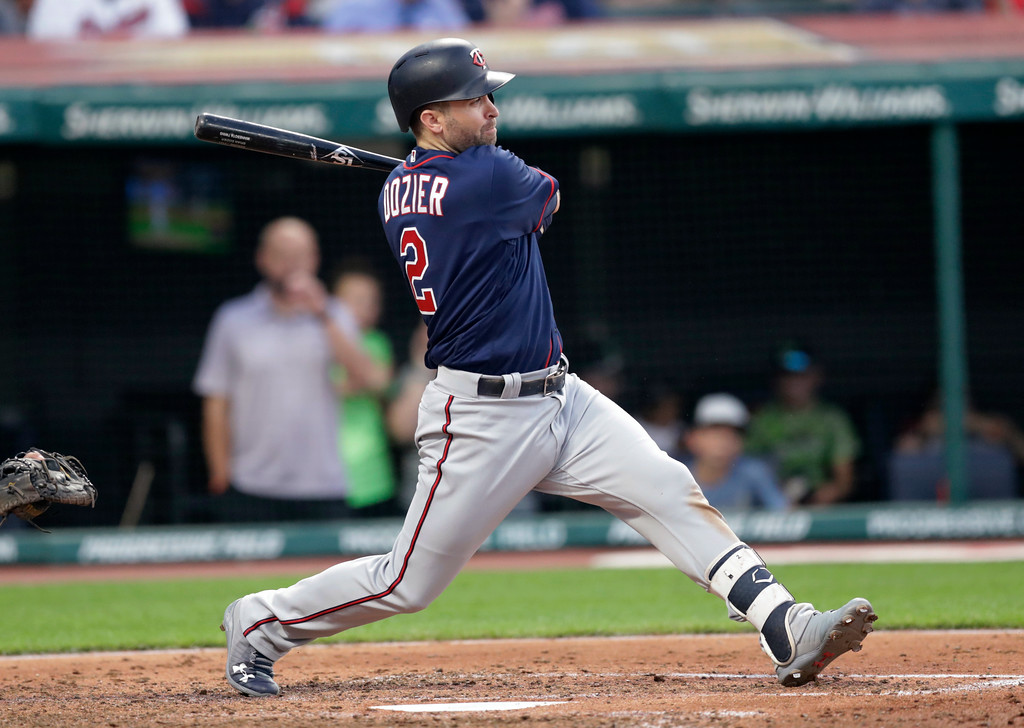 . Minnesota Twins\' Brian Dozier hits a grounder during the sixth inning of a baseball game against the Minnesota Twins, Friday, June 15, 2018, in Cleveland. Eduardo Escobar scored on the play. (AP Photo/Tony Dejak)