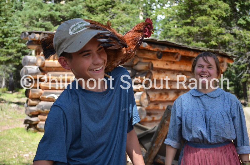 A scout is amused with the rooster perched on his shoulder at Crooked Creek.JPG
