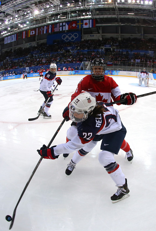 . Kacey Bellamy #22 of the United States handles the puck against Gillian Apps #10 of Canada in the third period during the Women\'s Ice Hockey Preliminary Round Group A game on day five of the Sochi 2014 Winter Olympics at Shayba Arena on February 12, 2014 in Sochi, Russia.  (Photo by Martin Rose/Getty Images)