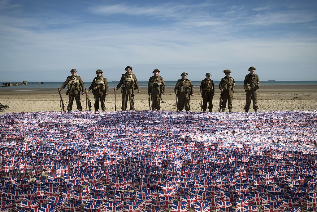 """. People wearing WWII British uniforms stand in front of 22.000 British national flags on June 6, 2014 in Asnelles, Normandy, during a ceremony on the \""""Gold beach\"""" where British troops landed on June 6, 1944 during the Operation Overlord.   AFP PHOTO / JOEL SAGET/AFP/Getty Images"""
