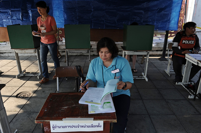 . A Thai voter (L) walks to cast her vote at a polling station in downtown Bangkok on February 2, 2014.  Polls opened on February 2 for tense elections in Thailand with opposition demonstrators preventing voting in parts of the country, a day after a gunfight between rival protesters in Bangkok raised fears of more violence. (CHRISTOPHE ARCHAMBAULT/AFP/Getty Images)