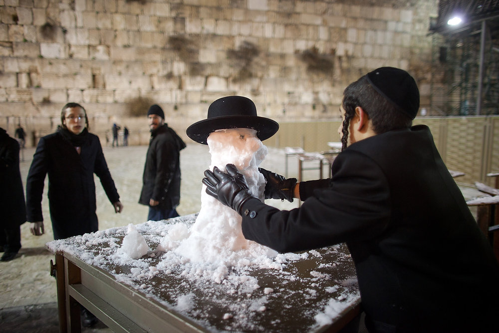 Description of . An ultra-Orthodox Jewish boy builds a snow man at the Western Wall on January 9, 2013 in Jerusalem, Israel. Snow and strong winds have affected regions across the Middle East.  (Photo by Uriel Sinai/Getty Images)