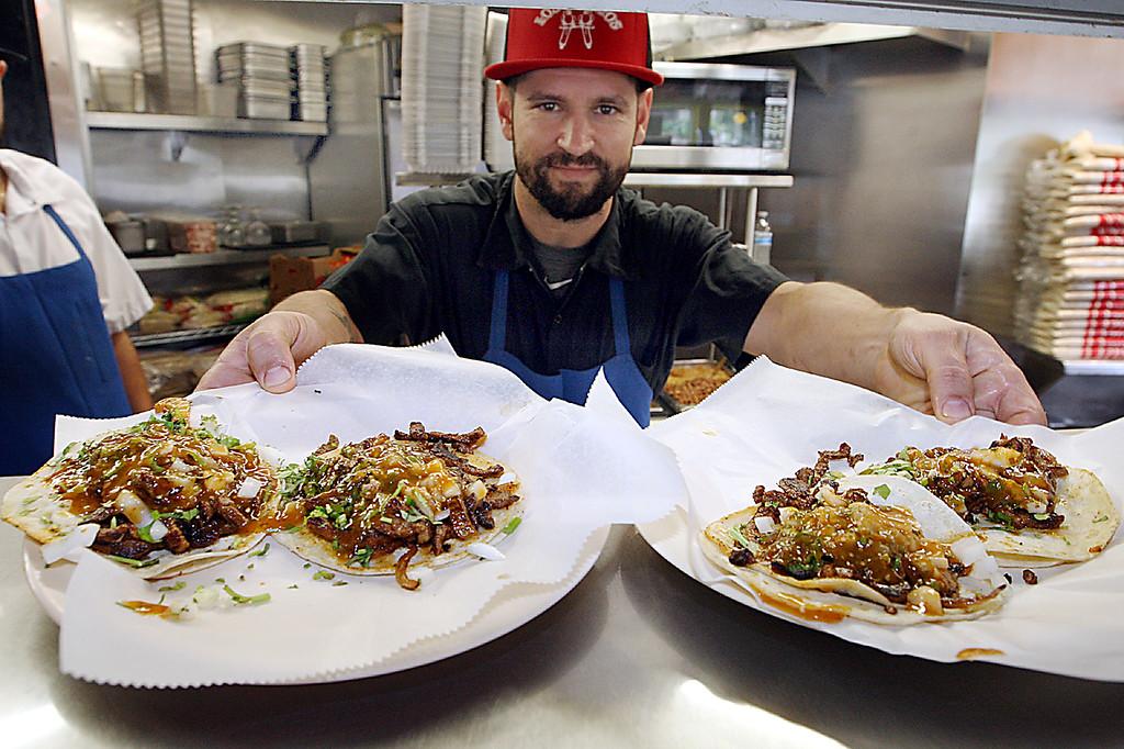 . Taqueria Los Pericos owner Jose Ruiz serves up some of his signature carne asada tocos from his downtown Santa Cruz restaurant. (Dan Coyro -- Santa Cruz Sentinel)