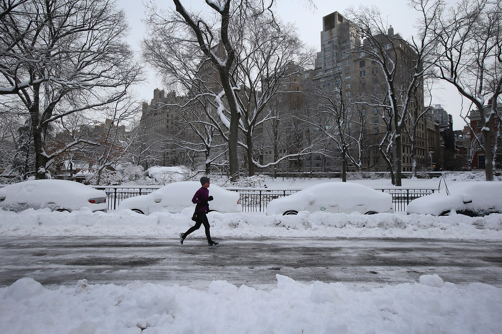. NEW YORK, NY - FEBRUARY 09:  A jogger passes snow-covered cars in Central Park on February 9, 2013 in New York City. The park received almost a foot of snow, as New York was spared the worst of the massive snow storm that hit the U.S. Northeast.  (Photo by John Moore/Getty Images)