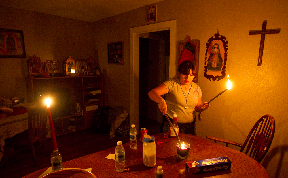 Description of . Dianna Herrera, 12, lights a small tree branch from a candle for light at her cousin Stephanie Lopez's home in Houston during a power outage on Tuesday, Dec. 25, 2012. Strong winds and rain-downed trees that were weakened by last year's drought knocked out power to tens of thousands of customers in the Houston area on Christmas Day. At the height of the storm, some 69,000 homes were without power in the Houston region.  By early evening CenterPoint Energy was reporting 52,000 customers were without power. (AP Photo/Houston Chronicle, Nick de la Torre)