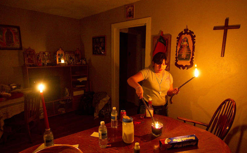. Dianna Herrera, 12, lights a small tree branch from a candle for light at her cousin Stephanie Lopez\'s home in Houston during a power outage on Tuesday, Dec. 25, 2012. Strong winds and rain-downed trees that were weakened by last year\'s drought knocked out power to tens of thousands of customers in the Houston area on Christmas Day. At the height of the storm, some 69,000 homes were without power in the Houston region.  By early evening CenterPoint Energy was reporting 52,000 customers were without power. (AP Photo/Houston Chronicle, Nick de la Torre)