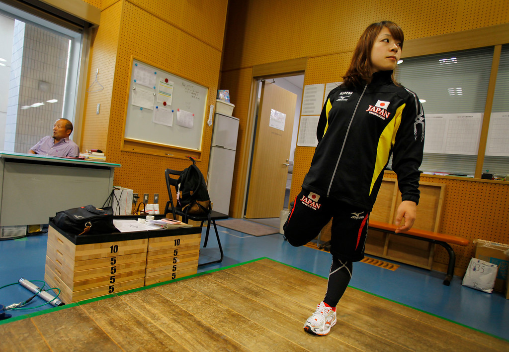 . In this Friday, Aug. 30, 2013 photo, Japanese weightlifter Hiromi Miyake, silver medalist in the London Olympic women\'s 48kg event, warms up before her training at one of Tokyo\'s leading training centers as her father and women\'s national team head coach Yoshiyuki Miyake looks on. The Olympics are in Hiromi Miyake\'s blood, a heritage that stretches back to the 1960s, when her uncle won a gold medal at the 1964 Tokyo Games and her father won bronze in Mexico City in 1968. (AP Photo/Junji Kurokawa)
