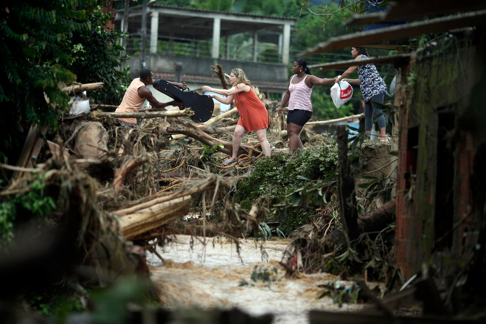 Description of . People carry their belongings after the floods of the Capivari river in Xerem, in Duque de Caxias near Rio de Janeiro January 3, 2013. At least 255 people were dislodged and one person died during the floods of Capivari River in Xerem, a district of Duque de Caxias, local media said.  REUTERS/Ricardo Moraes