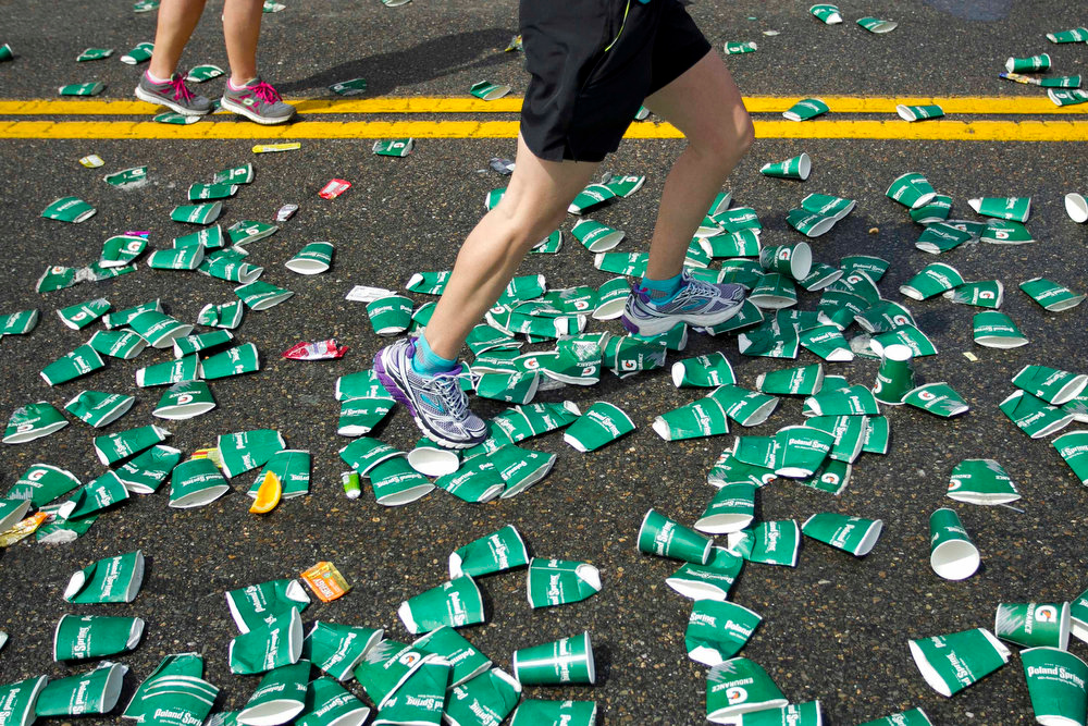 . A runner steps over discarded cups near a water station in the 117th running of the Boston Marathon in Wellesley, Massachusetts April 15, 2013. REUTERS/Dominick Reuter