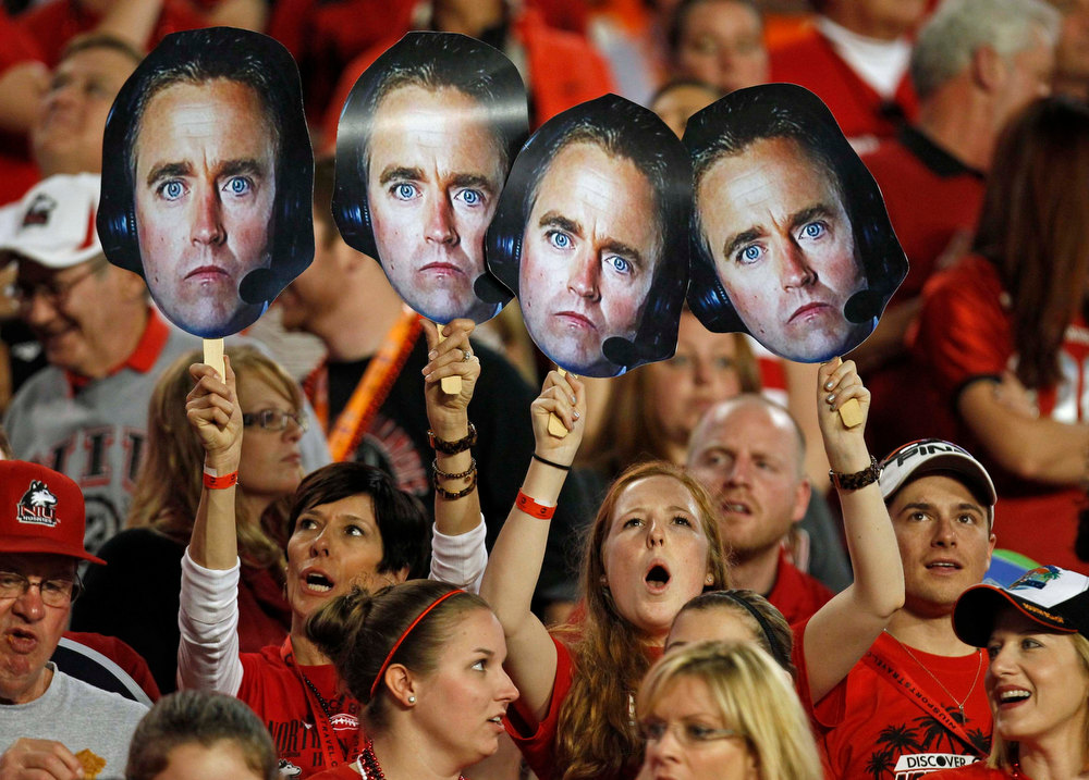 Description of . Northern Illinois Huskies fans hold cut-out pictures of ESPN broadcaster Kirk Herbstreit, who earlier called the inclusion of the Huskies in a BCS bowl a