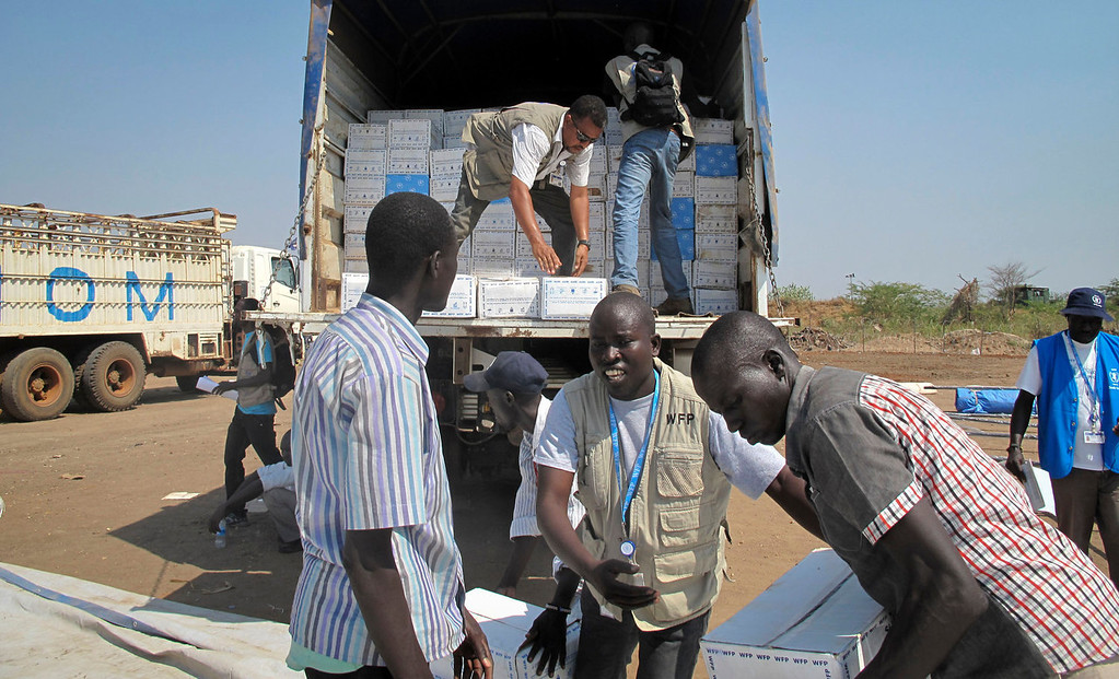 . In this photo released by the World Food Programme (WFP), staff and helpers unload a truck of cereal food assistance at a U.N. compound where many displaced have taken shelter in Juba, South Sudan, Tuesday, Dec. 24, 2013. South Sudan\'s military spokesman says there is increasing tension at a United Nations camp in the rebel-held city of Bor because armed elements have entered the congested area where the U.N. says about 17,000 civilians are seeking protection. (AP Photo/WFP, George Fominyen)