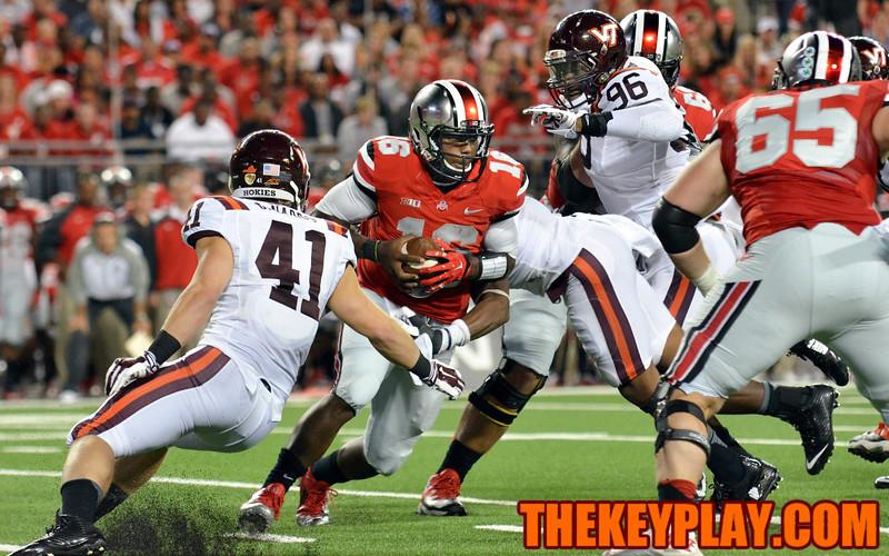 Ohio State Buckeyes quarterback J.T. Barrett (16) is surrounded and hit by Virginia Tech Hokies linebackers Deon Clarke (40) and Derek Di Nardo (41). (Michael Shroyer/ Thekeyplay.com)