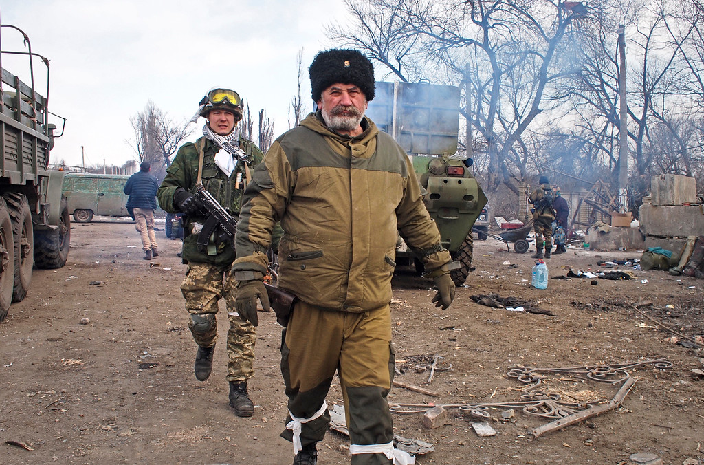 """. Cossack commander Nikolai Kozitsyn, foreground, a Russian national known to his fellow rebel fighters by the nom de guerre \""""Daddy,\"""" walks through a crossroads by the east Ukraine town of Debaltseve on Thursday, February 19, 2015. The town was captured by Russian-backed separatists this week after weeks of bitter battles around the area. (AP Photo/ Peter Leonard)"""