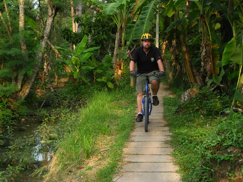 Greg rides a narrow path through a plantation