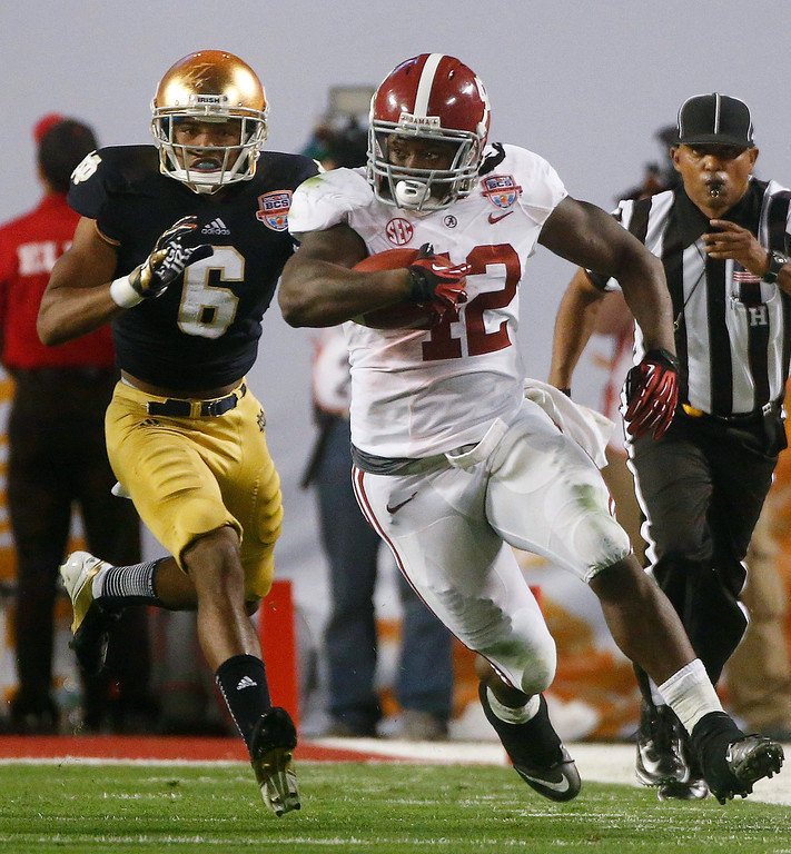 . Alabama\'s Eddie Lacy (42) runs past Notre Dame cornerback KeiVarae Russell during the second half of the BCS National Championship college football game Monday, Jan. 7, 2013, in Miami. (AP Photo/John Bazemore)