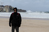 "The next day we took the ""Hop On Hop Off"" bus to tour Sydney.  Here's Steve at Bondi (pronounced Bond I) Beach, a world famous locale for the HUGE waves. Note the parka, gloves and pained expression.  That 's because it was probably 35 degrees with gale force winds.  It was a free microdermabrasion!"
