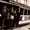 A busy trolley mid day February cruises SF main streets.