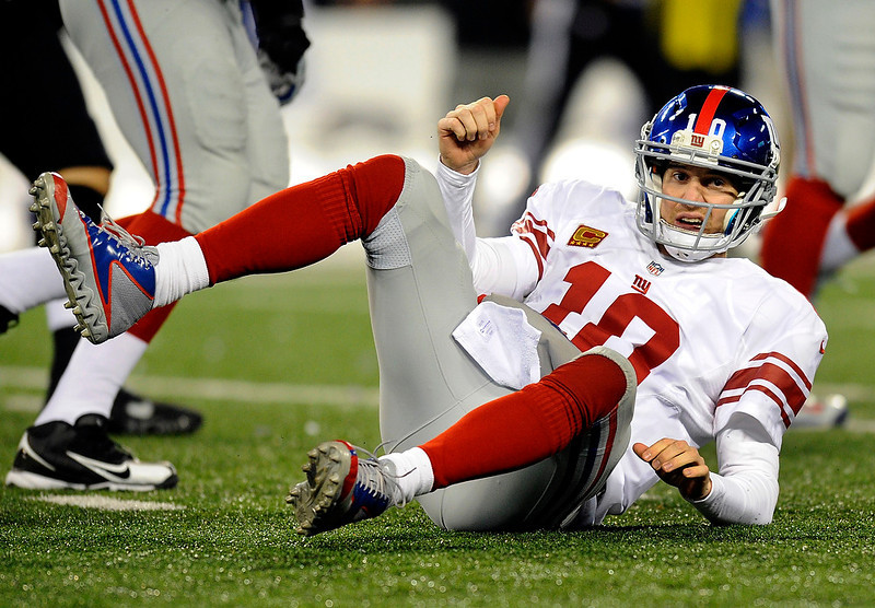 . New York Giants quarterback Eli Manning gets up after being tackled by Baltimore Ravens defensive end Arthur Jones while throwing to a receiver in the first half of an NFL football game in Baltimore, Sunday, Dec. 23, 2012. (AP Photo/Nick Wass)