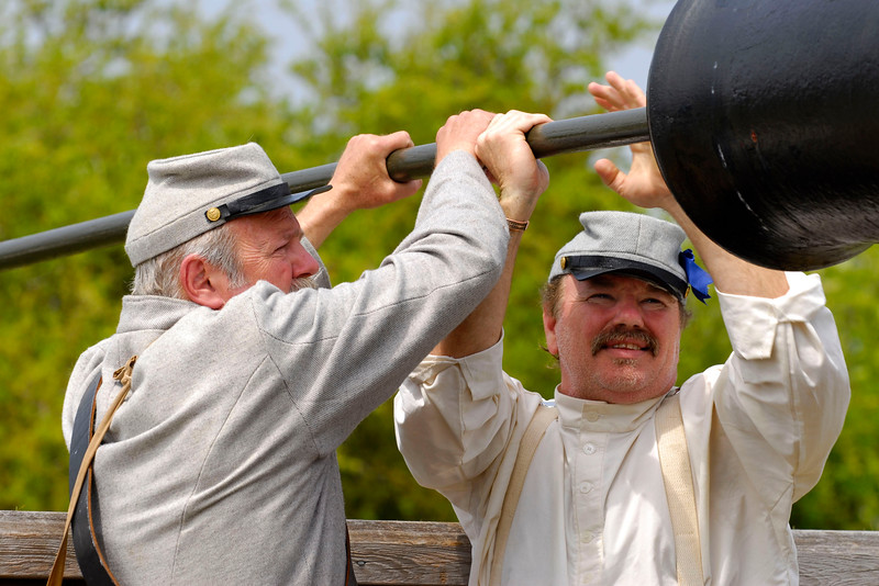 """Reenactors Rick Walker (left) and Laddie Parrish (right) ram """"powder"""" into the Model 1841 32-pound Smooth Bore canon at Ft. Moultrie in Sullivan's Island, South Carolina on Monday, April 11, 2011. ..The 150th Anniversary of the Firing on Ft. Sumter was commemorated with lectures, performances, demonstrations, and a living history throughout the area on James Island, Charleston, Mt. Pleasant, and Sullivan's Island during the week from April 8-14, 2011. Photo Copyright 2011 Jason Barnette"""
