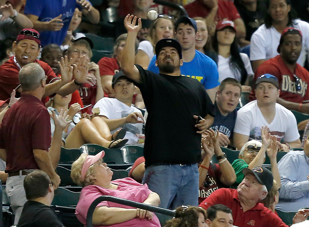 . A fan reaches for a foul ball during the sixth inning of a baseball game between the Los Angeles Dodgers and the Arizona Diamondbacks, Thursday, Sept. 19, 2013, in Phoenix. (AP Photo/Matt York)