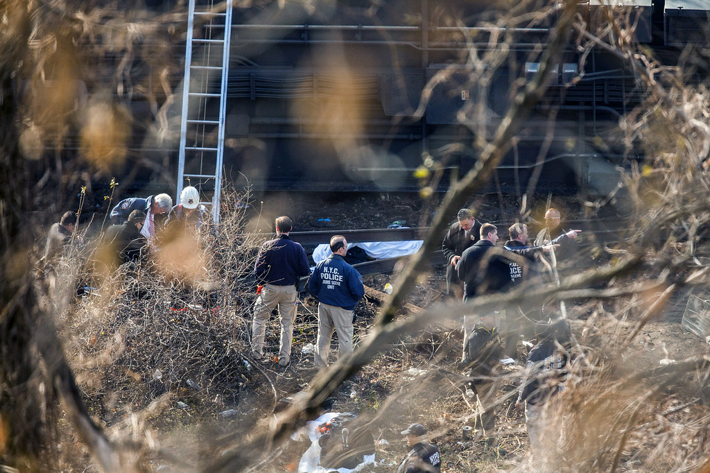 . NYC Police Crime Scene investigators stand near a covered body (C) after a Metro-North commuter train derailed just north of the Spuyten Duyvil station December 1, 2013 in the Bronx borough of New York City. Multiple injuries and at least 4 deaths were reported after the seven car train left the tracks as it was heading to Grand Central Terminal along the Hudson River line.  (Photo by Christopher Gregory/Getty Images)