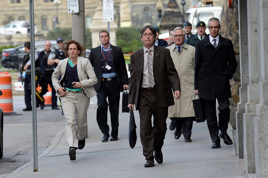 . Parliamentary staff leave the area after a shooting on Parliament Hill in Ottawa on Wednesday Oct. 22, 2014.  A soldier standing guard at the National War Memorial was shot by an unknown gunman and people reported hearing gunfire inside the halls of Parliament. Prime Minister Stephen Harper was rushed away from Parliament Hill to an undisclosed location, according to officials. (AP Photo/The Canadian Press, Adrian Wyld)