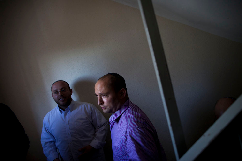 Description of . Naftali Bennett, right, head of the Jewish Home party, visits an apartment building during his election campaign, that was hit by a rocket fired by militants from Gaza Strip, last year, in the Israeli central city of Rishon Lezion, Israel, Monday, Jan. 21, 2013. The general elections will be held on Tuesday, Jan. 22, 2013. (AP Photo/Oded Balilty)