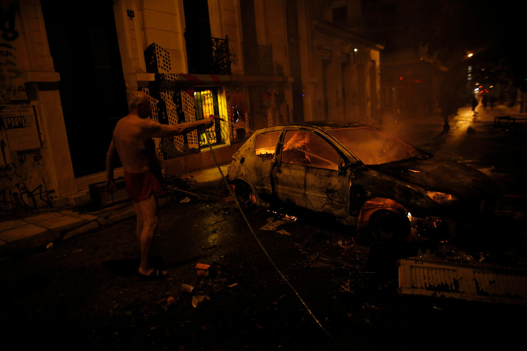 . A local resident in his underwear tries to extinguish a burning car used by protesters as a barricade, during riots in Athens neighborhood of Exarchia, a haven for extreme leftists and anarchists, on Saturday, Dec. 6, 2014. (AP Photo/Kostas Tsironis)