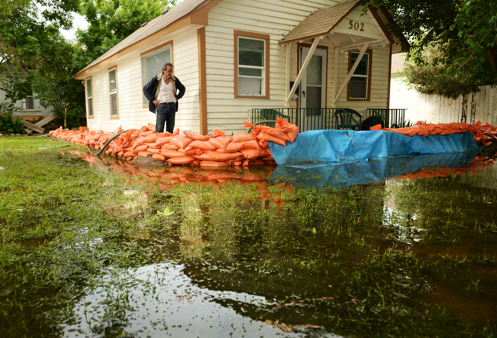 . Farr West checks on his sump pump outside his home in Greeley that is flooded by rising water along the Poudre River, June 4, 2014. A flood warning for the Poudre River near Greeley has been extended through Sunday. (Photo by RJ Sangosti/The Denver Post)