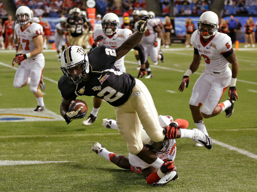 Description of . Central Florida wide receiver Jeff Godfrey (2) is tripped up by Ball State safety J.C. Wade (27) during the first quarter of the Beef 'O' Brady's Bowl NCAA college football game Friday, Dec. 21, 2012, in St Petersburg, Fla. (AP Photo/Chris O'Meara)