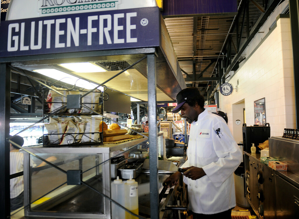 . Tyrone Titchenor works the gluten-free food stand on the third base side concourse at the  Denver  baseball park on May 3, 2013 before the Rockies game. (Photo By Cyrus McCrimmon/The Denver Post)
